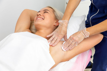 Fototapeta na wymiar beautician lubricates wax under the arms of the client. hair removal with wax