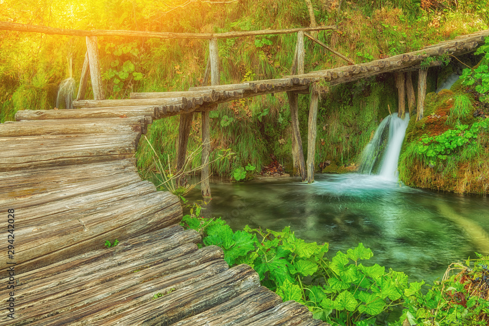 Deep forest stream with crystal clear water with wooden pahway and sunlight. Plitvice lakes, Croatia UNESCO world heritage site