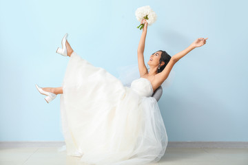 Happy young Asian bride near color wall