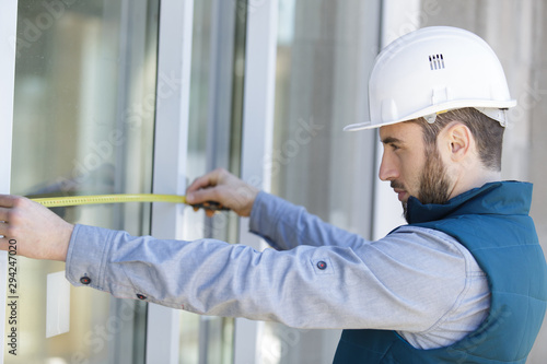 Valokuvatapetti man measuring window prior to installation of roller shutter outdoors
