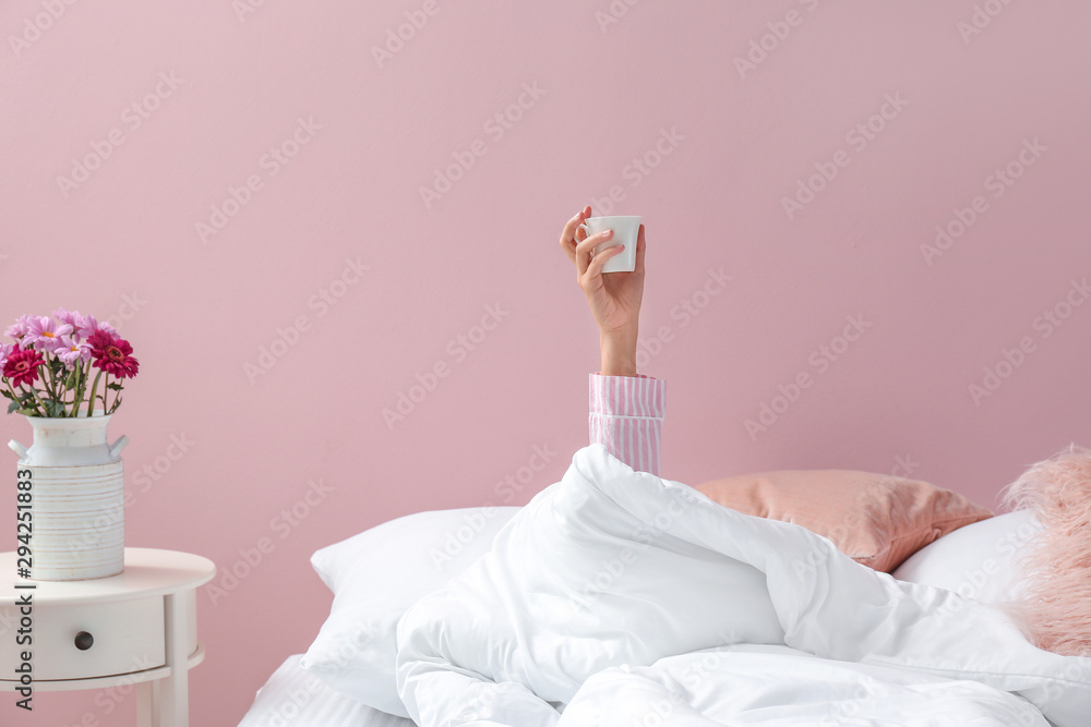 Fototapety, obrazy: Young woman with cup of coffee lying in bed