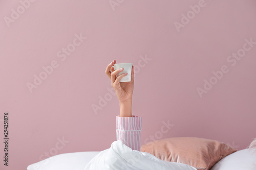 Obraz Young woman with cup of coffee lying in bed - fototapety do salonu