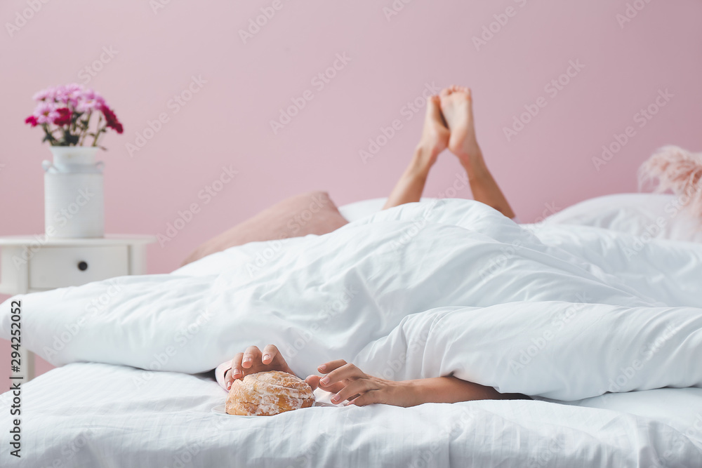 Fototapety, obrazy: Young woman reaching hands for tasty bun while lying in bed