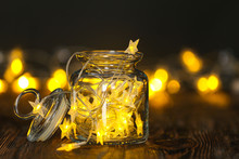 Jar With Glowing Garland On Wooden Table
