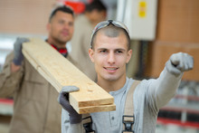 Two Men Carrying Planks Of Wood Together On Their Shoulders