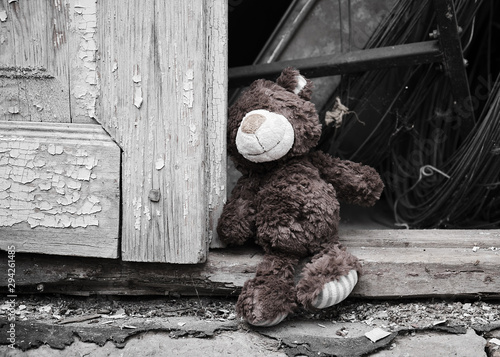 mata magnetyczna little teddy bear sits on the doorstep near an old door with cracked paint