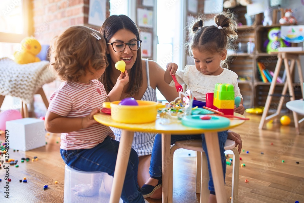 Fototapety, obrazy: Young beautiful teacher and toddlers playing meals using plastic food and cutlery toy at kindergarten