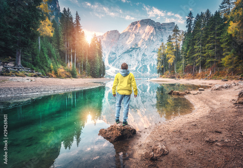 Foto auf Gartenposter Dunkelbraun Man is standing on the stone on Braies lake at sunrise in autumn. Dolomites, Italy. Landscape with guy, mountains, beautiful reflection in water, colorful trees, blue sky with sun. Forest in fall