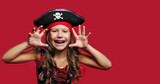 Close-up portrait of a pirate girl against red background