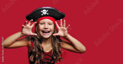 Close-up portrait of a pirate girl against red background Fototapeta