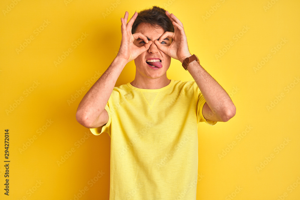 Fototapety, obrazy: Teenager boy wearing yellow t-shirt over isolated background doing ok gesture like binoculars sticking tongue out, eyes looking through fingers. Crazy expression.