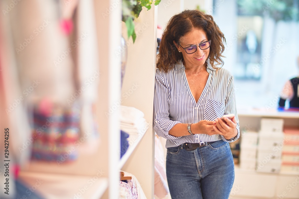 Fototapety, obrazy: Middle age beautiful businesswoman smiling happy and confident leaning on the wall using smartphone at clothes shop