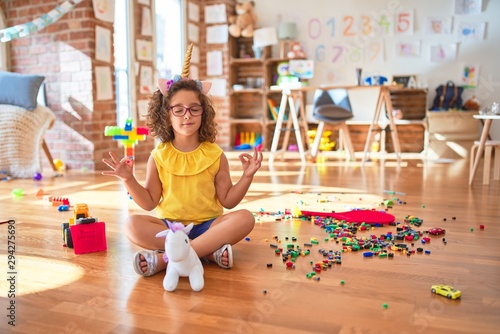 Beautiful toddler wearing glasses and unicorn diadem sitting on the floor at kindergarten relax and smiling with eyes closed doing meditation gesture with fingers Wallpaper Mural