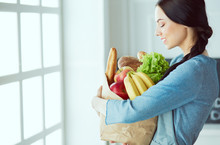 Young Housewife Hiding Behind Shopping Bag Full Of Vegetables