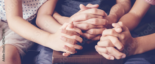 Fototapeta children praying with parent at home, family worship online together, hope, grat