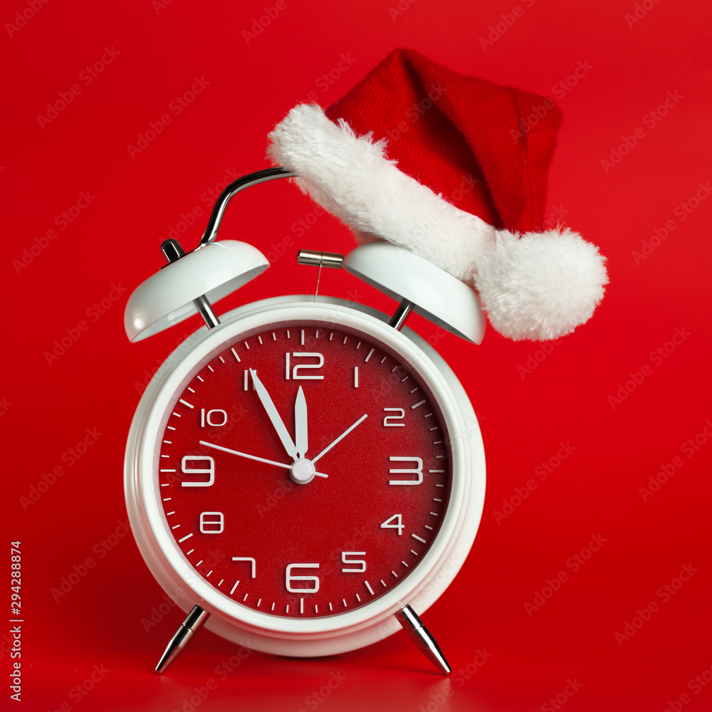 Fototapeta Red clock with Christmas Santa hat. Time for Christmas shopping concept.