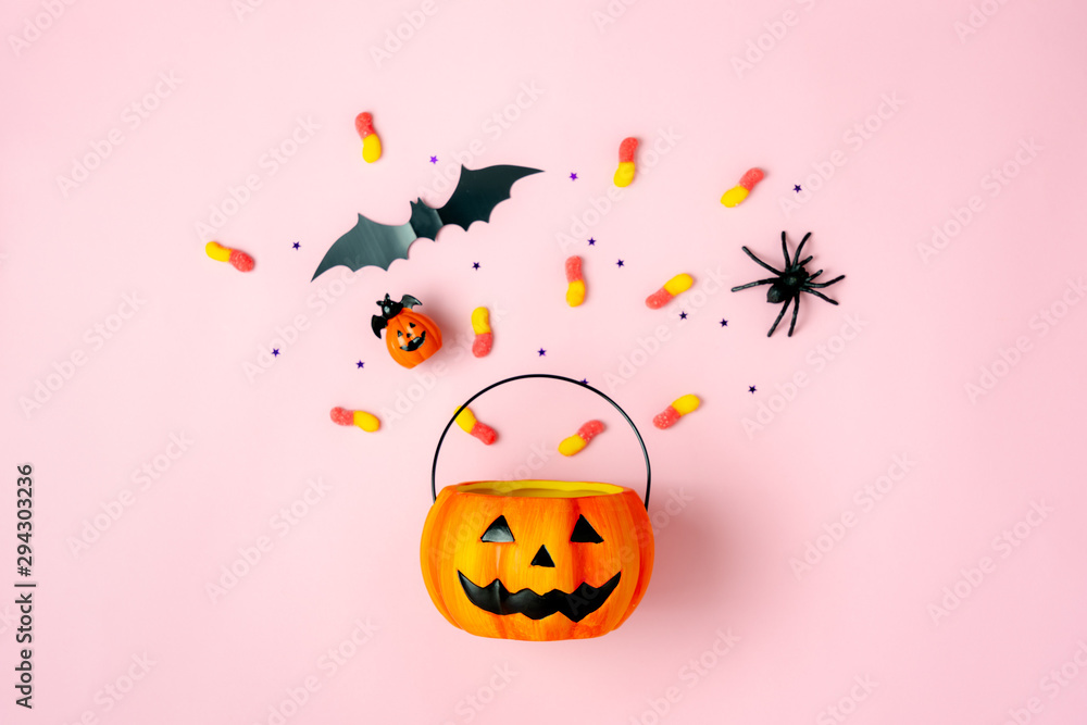Fototapeta Table top view aerial image of decorations Happy Halloween day background holiday concept.Flat lay objects to party Jack O lantern pumpkins bucket and spider with candy sweet on pink  paper.