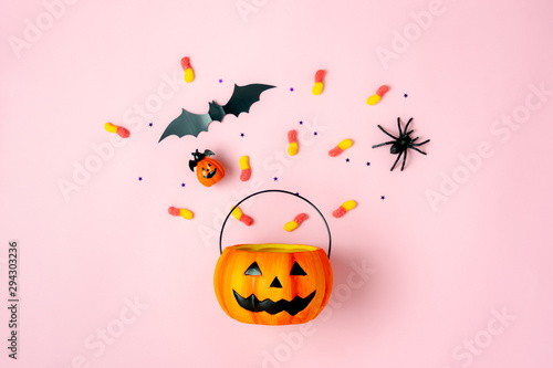 Table top view aerial image of decorations Happy Halloween day background holiday concept.Flat lay objects to party Jack O lantern pumpkins bucket and spider with candy sweet on pink paper.