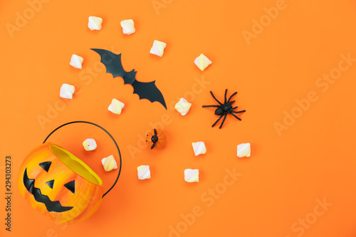 Table top view aerial image of decorations Happy Halloween day background holiday concept.Flat lay objects to party Jack O lantern pumpkin bucket and spider with candy sweet on orange paper.