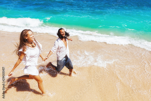 Cadres-photo bureau Ecole de Danse Happy family on honeymoon holiday - just married young couple having fun, run by water edge along sea beach surf. Active lifestyle, people recreational activity on summer vacation on tropical island.