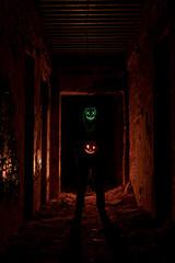 Man wearing glowing green scary mask standing in dark passage holding halloween pumpkin