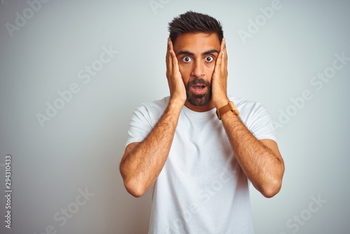 Young indian man wearing t-shirt standing over isolated white background afraid Tablou Canvas