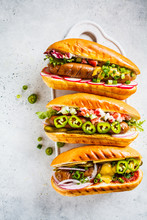 Hot Dogs With Different Toppings On White Background, Top View. Fast Food Concept.
