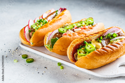Hot dogs with different toppings on white background Fototapeta