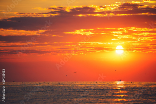 Poster Corail Sunrise over the sea with sailing fishing boat