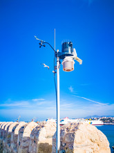 Anemometer Device Used For Measuring Wind Speed, Common Weather Station Instrument. Wind Speed Measurement  Meteorology Concept. Anemometer On Blue Sky Background.
