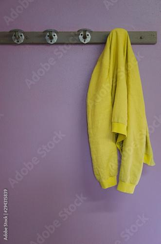 Fotomural une veste jaune accrochée à un porte-manteau sur un mur violet