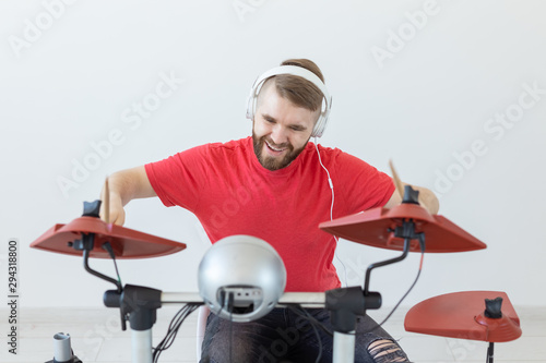 Fotomural Music, hobby and people concept - young man drummer playing the electronic drums