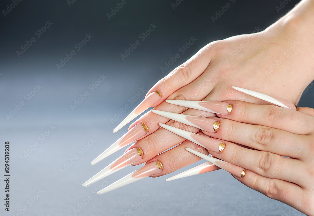 Beautiful long woman nails. White long nails. Special manicure skill.