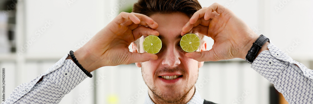 Fototapeta Male hands hold a cut fruit at eye level instead of glasses. The theme of a healthy diet for withdrawal activities and belief in diet achievements in business and education.