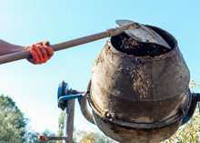 Man Adding Components To A Cement Mixer