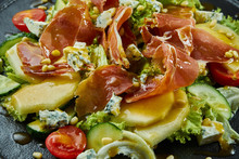 Close Up View On Salad With Honey Pear, Dor Blue Cheese And Prosciutto On Stylish Dark Plate On Black Wooden Background. Selective Focus