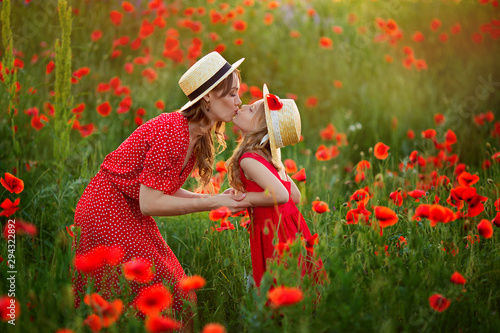 Beautiful mother and daughter in straw hats and red dresses kiss each other in spring on a poppy field in the mountains.