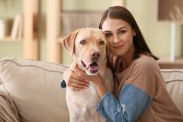 FototapetaBeautiful young woman with cute dog at home
