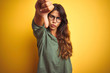 Leinwanddruck Bild - Young beautiful woman wearing green shirt and glasses over yelllow isolated background looking unhappy and angry showing rejection and negative with thumbs down gesture. Bad expression.