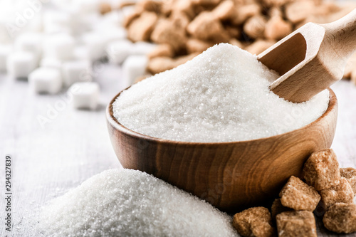 Fotografia White sugar in wooden bowl with scoop on white table