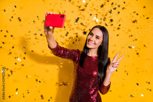 Portrait of nice attractive charming glamorous gorgeous winsome cheerful cheery girl holding in hands cell making selfie showing v-sign isolated on bright vivid shine vibrant yellow color background