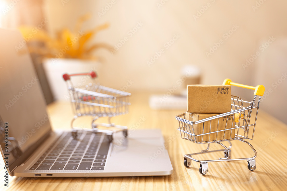 Fototapeta Online shopping and delivery service concept.Brown paper boxs in a shopping cart with laptop keyboard on wood table in office background.Easy shopping with finger tips for consumers.