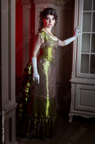 Fotomural Beautiful young woman in retro style, her dress is olive color.