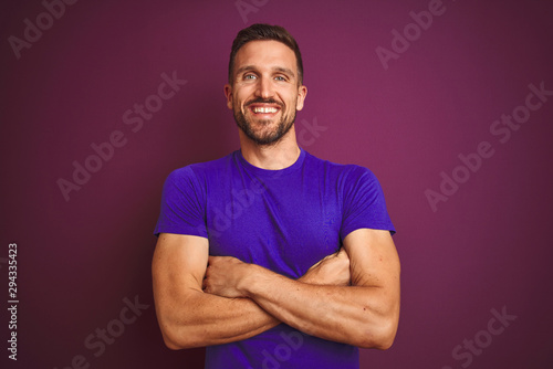 Fotografía  Young man wearing casual purple t-shirt over lilac isolated background happy face smiling with crossed arms looking at the camera