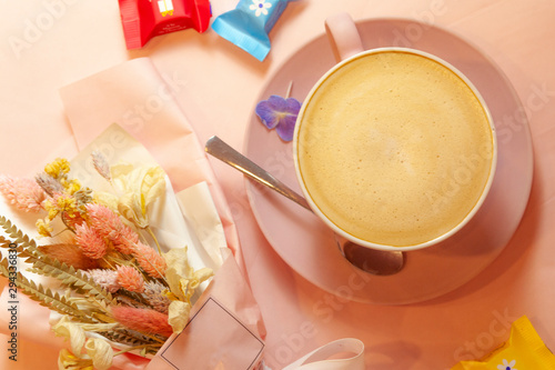 The cup of coffee with flowers and candys on the pink background