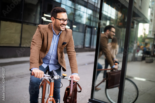 Happy businessman riding bicycle to work in morning Canvas Print