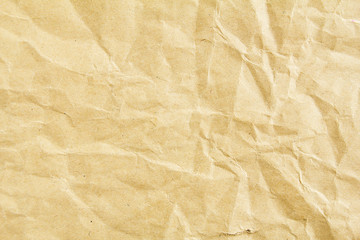 Closeup crumpled brown beige sheet of craft wrapping paper texture background.