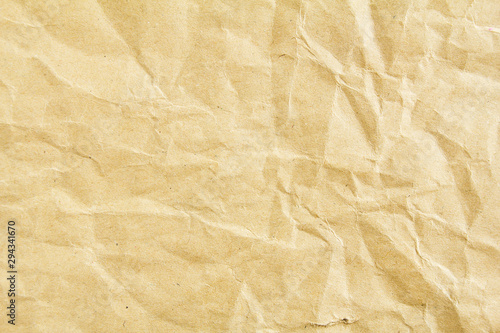 Closeup crumpled brown beige sheet of craft wrapping paper texture background Wallpaper Mural