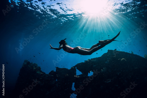 Fotografia Free diver girl in pink swimwear with fins swimming underwater at wreck ship