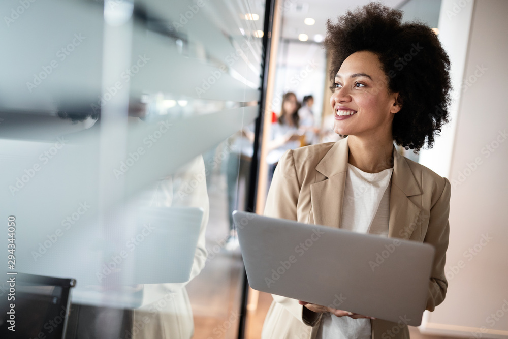 Fototapeta Portrait of an attractive young african businesswoman smiling while standing by windows in office
